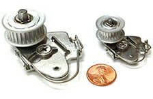 two small aluminum tensioners with penny for size
